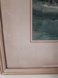 Discolouration on the mount of a picture in a frame
